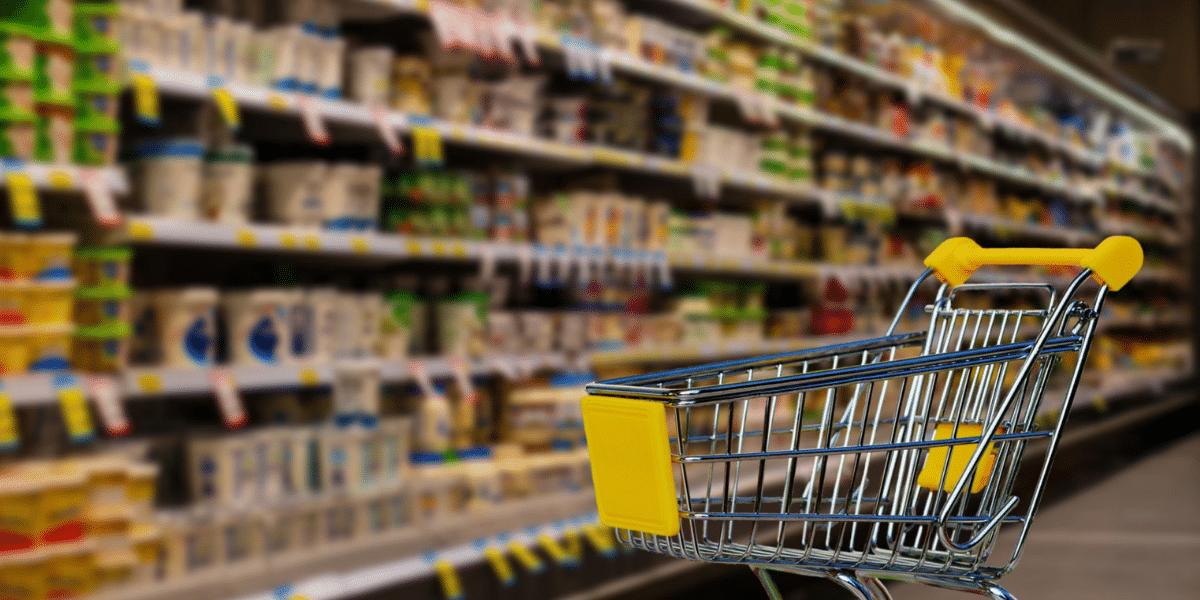 shopping cart in front of a grocery aisle